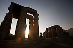 A male tourist wearing a hat visits the Ramesseum, or memorial temple of Ramses II, at sunset on the West Bank of Luxor, Egypt, near the Nile River.
