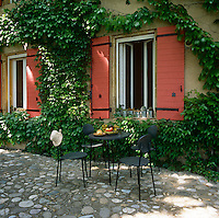 A table and chairs stands on a stone terrace outside a country house. A creeper growns up the walls and around the window shutters.