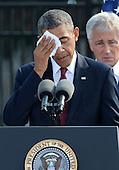 United States President Barack Obama wipes his brow due to the very hot and humid weather during his remarks at the 12th anniversary commemoration of the 9/11 terrorist attacks at the Pentagon Memorial at the Pentagon in Washington, DC on September 11, 2013. Nearly 3,000 people were killed in the attacks in New York, Washington and Shanksville, Pennsylvania. Behind Obama is U.S. Secretary of Defense Chuck Hagel.   <br /> Credit: Pat Benic / Pool via CNP