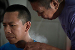 Ovidio Barreto, a Tukano indigenous healer, blows smoke on Humberto Peixoto, a Tuyuka Indian, during a treatment in the  Bahse Rikowi Center for Indigenous Medicine in Manaus, Brazil.