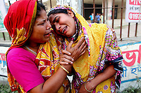 Two women cry for their dead and missing relatives outside the collapsed Rana Plaza complex in Savar. The 8 storey building, which housed a number of garment factories employing over 3,000 workers, collapsed on 24 April 2013. By 29 April, at least 380 were known to have died while hundreds remained missing. Workers who were worried about going to work in the building when they noticed cracks in the walls were told not to worry by the building's owner, Mohammed Sohel Rana, who is a member of the ruling Awami League's youth front. He fled his home and tried to escape to neighbouring India after the building collapsed but was caught by police and brought back to Dhaka. Some of the factories working in the Rana Plaza building produce cheap clothes for various European retailers including Primark in the UK and Mango, a Spanish label. . /Felix Features