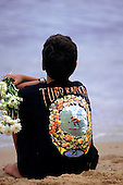 Salvador, Bahia, Brazil. Boy sitting on the beach holding a bunch of flowers, wearing a surfing t-shirt.