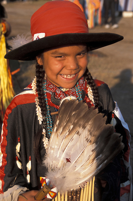 Young Canadian Blackfeet Tribal member in traditional tall reservation hat covered in a red scarf holding an eagle wing dance fan during the annual Blackfeet Indian Days Pow Wow in Browning Montana