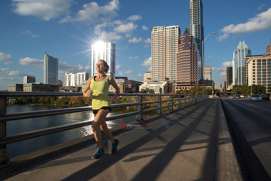 Athlete running on the Congress Avenue Bridge. Action shot of runner in downtown Austin with sunny blue skies. healthy lifestyle fitness woman