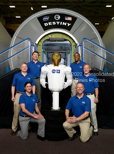 """The National Aeronautics and Space Administration's (NASA) Robonaut 2, or R2 for short, who will hitch a ride with the STS-133 crew members to travel to the International Space Station for a tour of duty beginning this fall, """"poses"""" near a Destiny lab trainer with the crew during a break in training on June 28, 2010. Clockwise from lower right, R2 is flanked by NASA astronauts Tim Kopra and Nicole Stott, both mission specialists; Eric Boe, pilot; Michael Barratt and Alvin Drew, both mission specialists, and Steve Lindsey, commander. STS-133, aboard the Space Shuttle Discovery, is scheduled for launch Monday, November 1, 2010 at 4:40 p.m. EDT..Mandatory Credit: Robert Markowitz / NASA via CNP"""