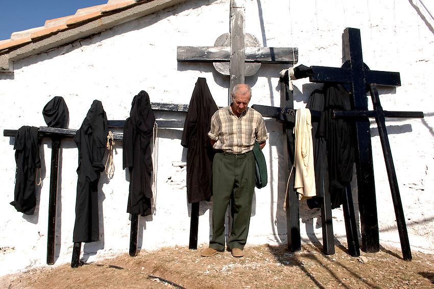 IRUNBERRI - LUMBIER, NAVARRE - JUNE 11: A man stands near the penitents  black monks habits during the celebration of the 'Cruceros' brotherhood penitential pilgrimage to the 'Ermita de la Trinidad' on June 11, 2006 in Irunberri - Lumbier, Navarre. Photo by Ander Gillenea