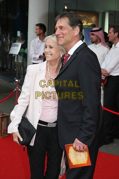 SUSAN GEORGE & SIMON MacCORKINDALE .Royal Film Premiere of 'Arabia 3D' at the BFI Imax cinema, Waterloo, London, England, UK, May 24th 2010 . .arrivals half length pink jacket black suit red tie smiling clutch bag side profile .CAP/MAR.© Martin Harris/Capital Pictures.