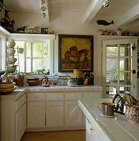 The kitchen has white-painted wooden units and work surfaces tiled with simple white ceramic tiles