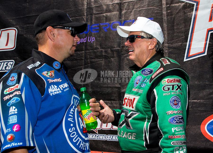 Jun. 1, 2014; Englishtown, NJ, USA; NHRA funny car driver Robert Hight (left) talks with teammate John Force during the Summernationals at Raceway Park. Mandatory Credit: Mark J. Rebilas-