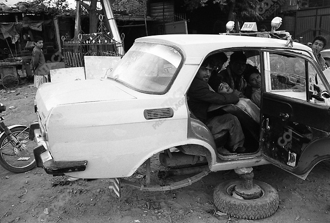 Teenagers hanging out in a car being repaired in central Kabul, Afghanistan, September 2005..