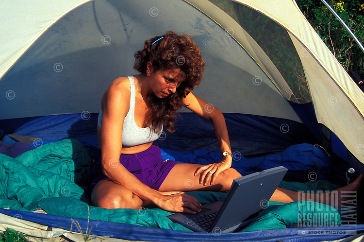 Woman looking at her laptop while in a tent camping in daylight