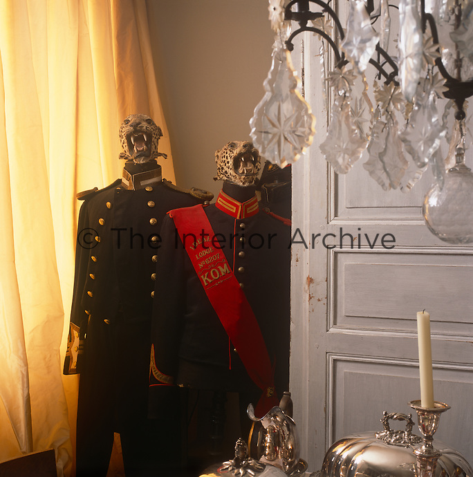Two vintage military unifroms displayed on stands in the corner of a room. In the foreground hangs a crystal chandelier.