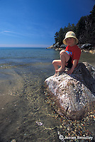 Little girl sitting on a rock on the lakeshore