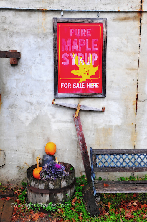 Colorful maple syrup sign leaning against wall.  Digitally enhanced.