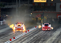 Oct 31, 2015; Las Vegas, NV, USA; NHRA funny car driver Brandon Welch (left) explodes an engine on fire alongside Jeff Arend during qualifying for the Toyota Nationals at The Strip at Las Vegas Motor Speedway. Mandatory Credit: Mark J. Rebilas-USA TODAY Sports
