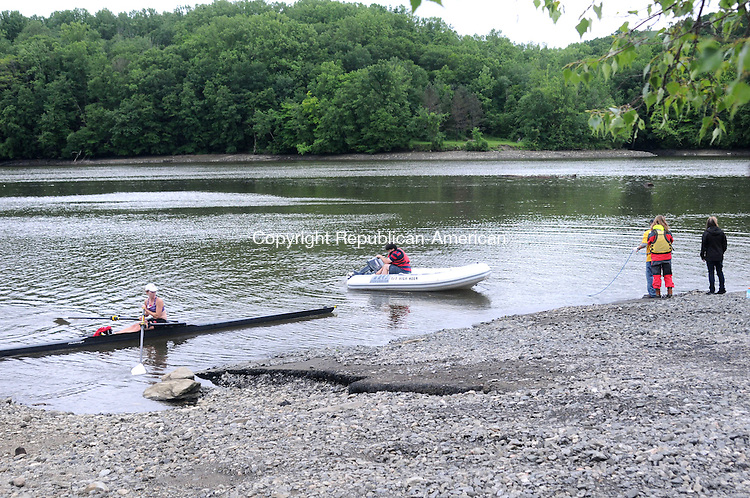 BRIDGEWATER, CT, 14 JUNE 13- 061413AJ02- Friends of Eric Langlois load an inflatable boat into Lake Lillinonah Friday morning as a rower, out for crew practice on the morning's flat water, makes her way back to shore.   Alec Johnson/ Republican-American