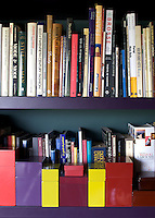 The made-to-measure bookcase in the library has been lacquered a deep aubergine, the perfect foil for some vivid storage boxes