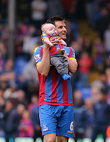 Pictured: Scott Dann of Crystal Palace with his young baby thanks supporters after the end of the game<br />