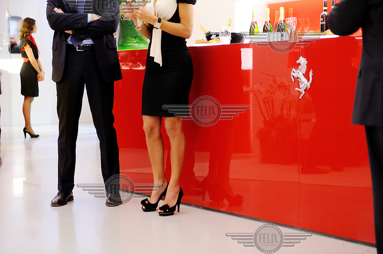 A couple stand and talk by the bar inside the Ferrari stand at the Geneva Motor Show.