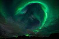 Northern Lights - Aurora Borealis circle in sky over mountains of Flakstadøy, Lofoten Islands, Norway