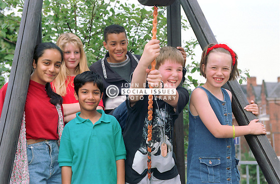 Multiracial group of young children standing together on climbing frame,