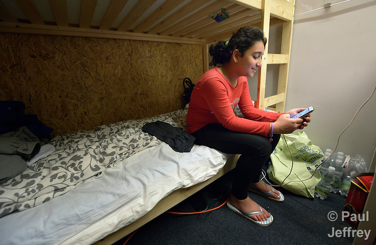Twelve-year old Sara Altaie checks messages on her mobile phone in her family's room in a refugee shelter in Vienna, Austria. While the application of her family for asylum is being considered, the Iraqi family lives in this temporary shelter constructed in a branch of the Erste Bank. <br /> <br /> The shelter is coordinated by Johanniter-Unfall-Hilfe &Ouml;sterreich, a member of the Diakonie network in Austria, which is a member of the ACT Alliance. Some 85 refugees currently live in the former bank, and several bank employees volunteer to assist the refugees sheltered there.