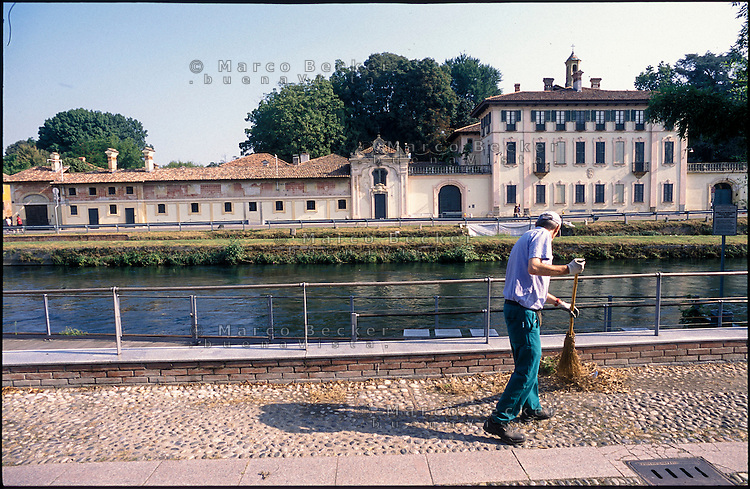 Cassinetta di Lugagnano (Milano). Uno spazzino al lavoro lungo il Naviglio Grande di fronte a Villa Visconti  --- Cassinetta di Lugagnano (Milan). A street cleaner at work along the canal Naviglio Grande in front of Villa Visconti