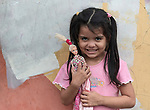 Ana Rebecca, age 5, holds a doll as she poses for a photo in her family's one-room apartment in a building in Manaus, Brazil. Her Kokama indigenous family migrated to the city in 2018, but unable to find decent housing they could afford, they joined with other poor families to take over an unoccupied building--the Casa do Estudante--in the city center. Caritas, a ministry of the Catholic Church, has helped the families in their struggle.<br /> <br /> Written parental consent obtained.