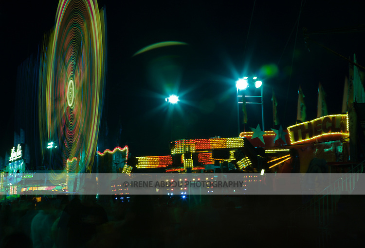 A slower shutter speed (4.0 sec) captures the full glory of these carnival rides in motion at the annual Montgomery County Agricultural Fair in Gaithersburg, Maryland.  A small aperture (f/22) renders the bright lights into stars.
