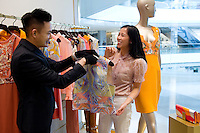 HONG KONG - MAY 04: Patricia Szeto tries on clothes in a fashion store in IFC (International Finance Center) shopping mall in Central business district, on May 4, in Hong Kong. (Photo by Lucas Schifres/Pictobank)