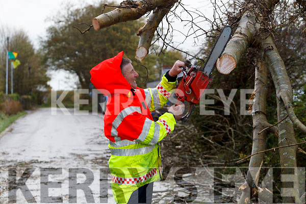 Tom Bowler cutting up a tree blocking the road in Lixnaw during Storm Ophilia on Monday.