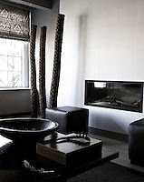The TV room has a tougher more urban aesthetic and is furnished with black leather pouffes