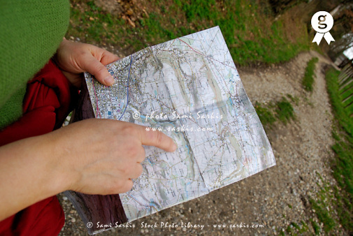 Woman on country road pointing finger on map, mid section (Licence this image exclusively with Getty: http://www.gettyimages.com/detail/sb10065145r-001 )