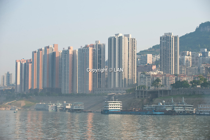 Daytime landscape view of the Cháng Jiāng with commercial buildings in the background at the Tiancheng migration development area in the Wànzhōu District in the Chongqing Municipality.  © LAN