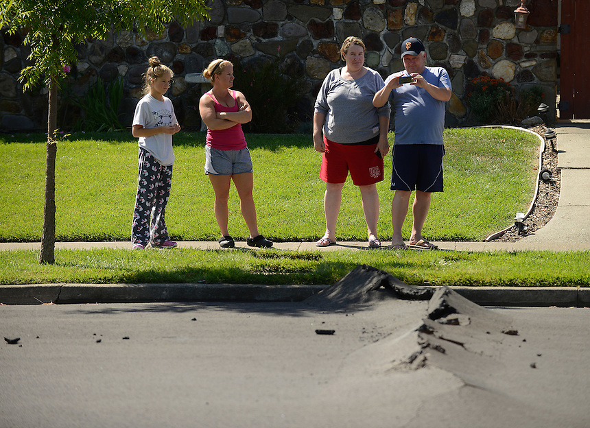 Makenna Harpe, left, age 13, and her mother Kelli talk with neighbors Kirsten and Toby Rompel as Toby snaps a photo of the buckled pavement on their street after a magnitude 6.0 earthquake struck in the early morning of August 24, 2014, in Napa, California.