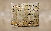 Photo of Hittite monumental relief sculpted orthostat stone panel of Procession. Limestone, Karkamıs, (Kargamıs), Carchemish (Karkemish), 900-700 B.C. Anatolian Civilisations Museum, Ankara, Turkey.<br /> <br /> Musicians. Two musicians with short arms, wearing long dresses and wide belts; one plays a Saz (a stringed musical instrument) with tassels on the handle while the other plays the flute. The third small figure holds castanets (?) in his hands. The figure on the right wears a short skirt, contrary to the others. She dances over her finger tips with her hands over her head. <br /> <br /> Against a brown art background.