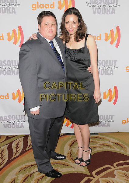 CHAZ BONO & JENNIFER ELIA .at the 21st Annual GLAAD Media Awards held at The Hyatt Regency Century Plaza in Century City, California, USA, April 17th 2010.       .full length suit grey gray blue tie striped pinstripe white shirt couple fiancee arm around shoulder black dress                                            .CAP/RKE/DVS.©DVS/RockinExposures/Capital Pictures.