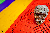 A painted, Aztec-inspired skull is placed above chiseled paper flags (papel picado) on the market stall during the Day of the Dead festivities in Mexico City, Mexico, 28 October 2016. Skulls, skeletons and the other death symbols are used to adorn graves, altars and offerings during the Day of the Dead (Día de Muertos). A syncretic religious holiday, combining the death veneration rituals of the ancient Aztec culture with the Catholic practice, is celebrated throughout all Mexico. Based on the belief that the souls of the departed may come back to this world on that day, people gather at the gravesites in cemeteries, praying, drinking and playing music, to joyfully remember friends or family members who have died and to support their souls on the spiritual journey.