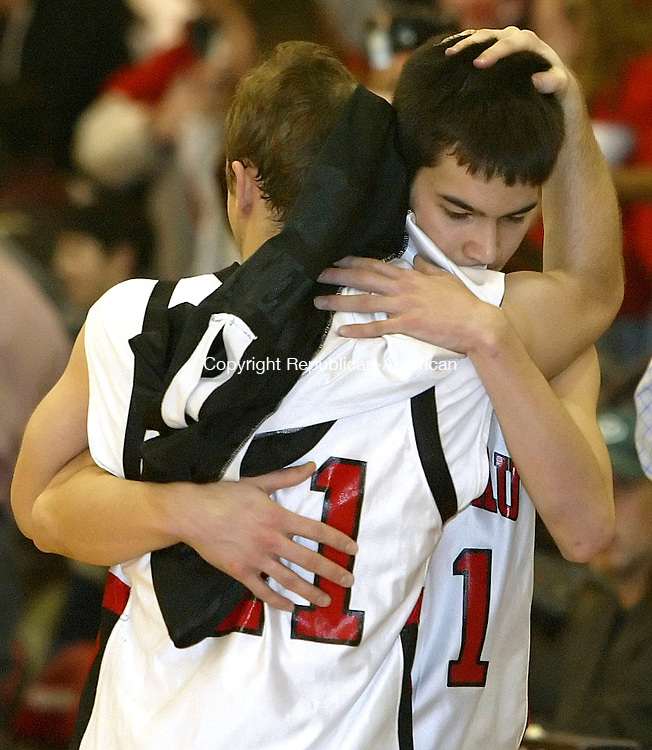 SOUTHBURY, CT, 03/07/07- 030707BZ6- Pomperaug's Bryan Wrabel (41) hugs teammate Ken Pun (21) after losing 51-44 to E.O. Smith during the second round of the Class L tournament at Pomperaug High School Thursday night.<br /> Jamison C. Bazinet Republican-American