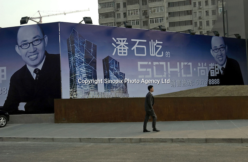 A man walks past a huge billboard featuring Pan Shiyi, boss of SOHO China Ltd., and his new commercial skyscrape in Beijing, China..21-JAN-05