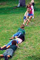Group of six kids playing tug of war with rope