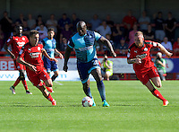 Adebayo Akinfenwa of Wycombe Wanderers takes on Jimmy Smith of Crawley Town (left) and Mark Connolly during the Sky Bet League 2 match between Crawley Town and Wycombe Wanderers at Broadfield Stadium, Crawley, England on 6 August 2016. Photo by Alan  Stanford / PRiME Media Images.