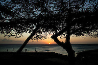 Sunset along the shores of Aruba. Aruba remains a popular tourist destination, with international planes and cruise ships arriving daily. Aruba, part of the Lesser Antilles, is famous for its white sand beaches, blue/green waters and mild climate.