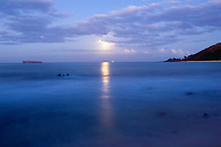 Full moon sets at Big Beach, Makena, Maui, Hawaii.