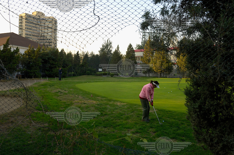 A woman putting on a practice green at Chaoyang golf club.