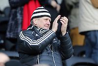 SWANSEA, WALES - FEBRUARY 07: A Swansea supporter applauds players as theywalk off the pitch after the Premier League match between Swansea City and Sunderland AFC at Liberty Stadium on February 7, 2015 in Swansea, Wales.