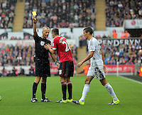 Pictured L-R: Match referee Martin Atkinson shows Morgan Schneiderlin of Manchester United a yellow card for his foul on Jack Cork of Swansea Sunday 30 August 2015<br /> Re: Premier League, Swansea v Manchester United at the Liberty Stadium, Swansea, UK