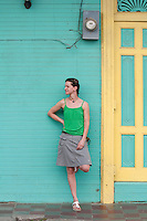Young woman leaning against brightly colored wall, San Juan Del Sur, Nicaragua