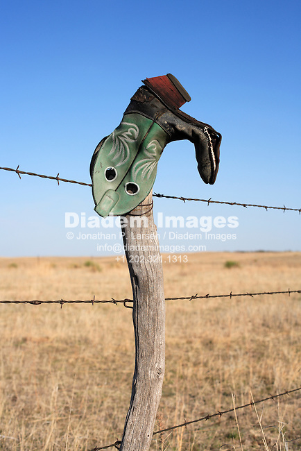 An upside down cowboy boot on a ranch fence in rural Nebraska, USA.