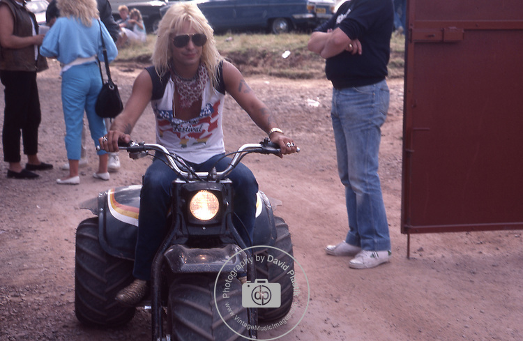 Vince Neil of Motley Crue backstage riding a motorcycle at Monsters of Rock Festival Aug 1984 , Castle Donnington, England Donnington Monsters of Rock 1984 Donnington 1984